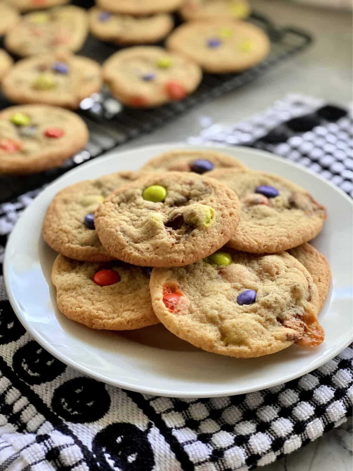 Close up of a plate of cookies with candies in them and more cookies in the background.