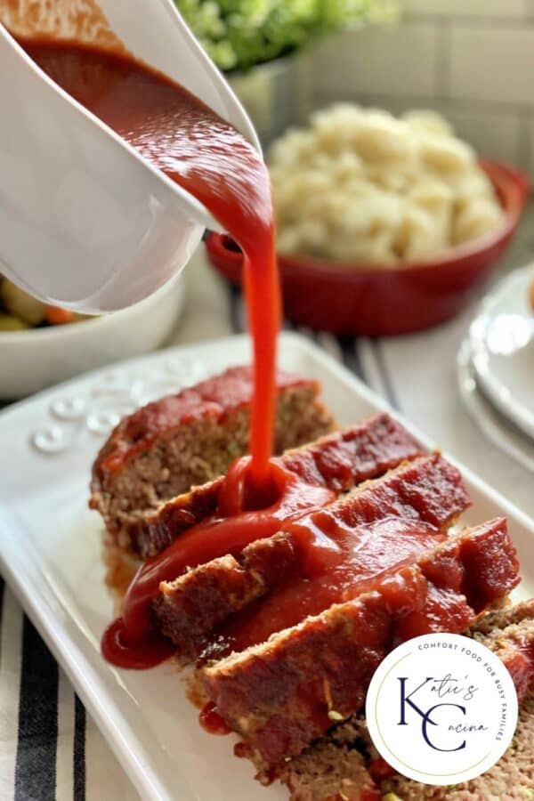White gravy boat pouring red sauce on top of sliced meatloaf.