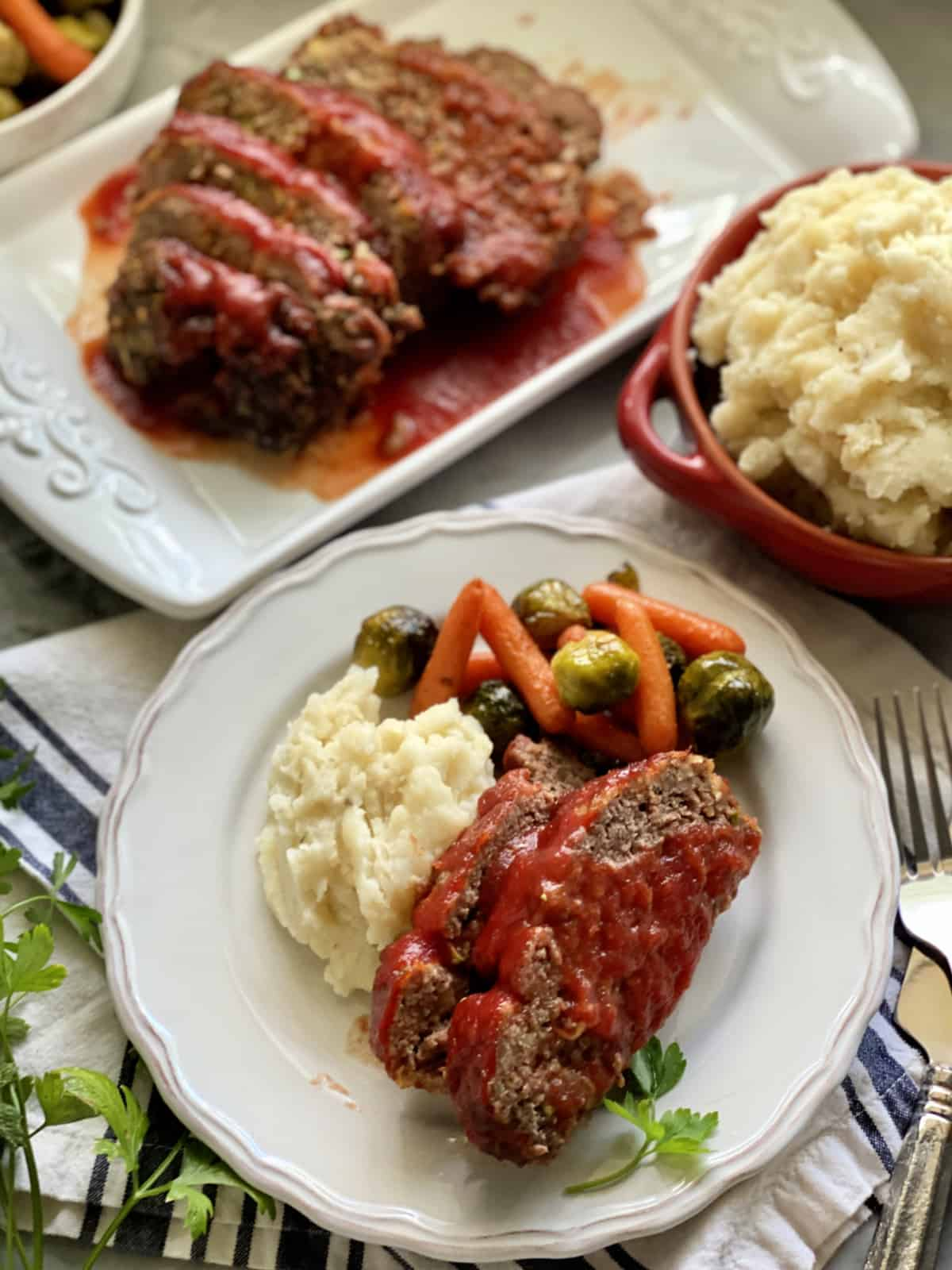 Top view of a plate of meatloaf with mashed potatoes.