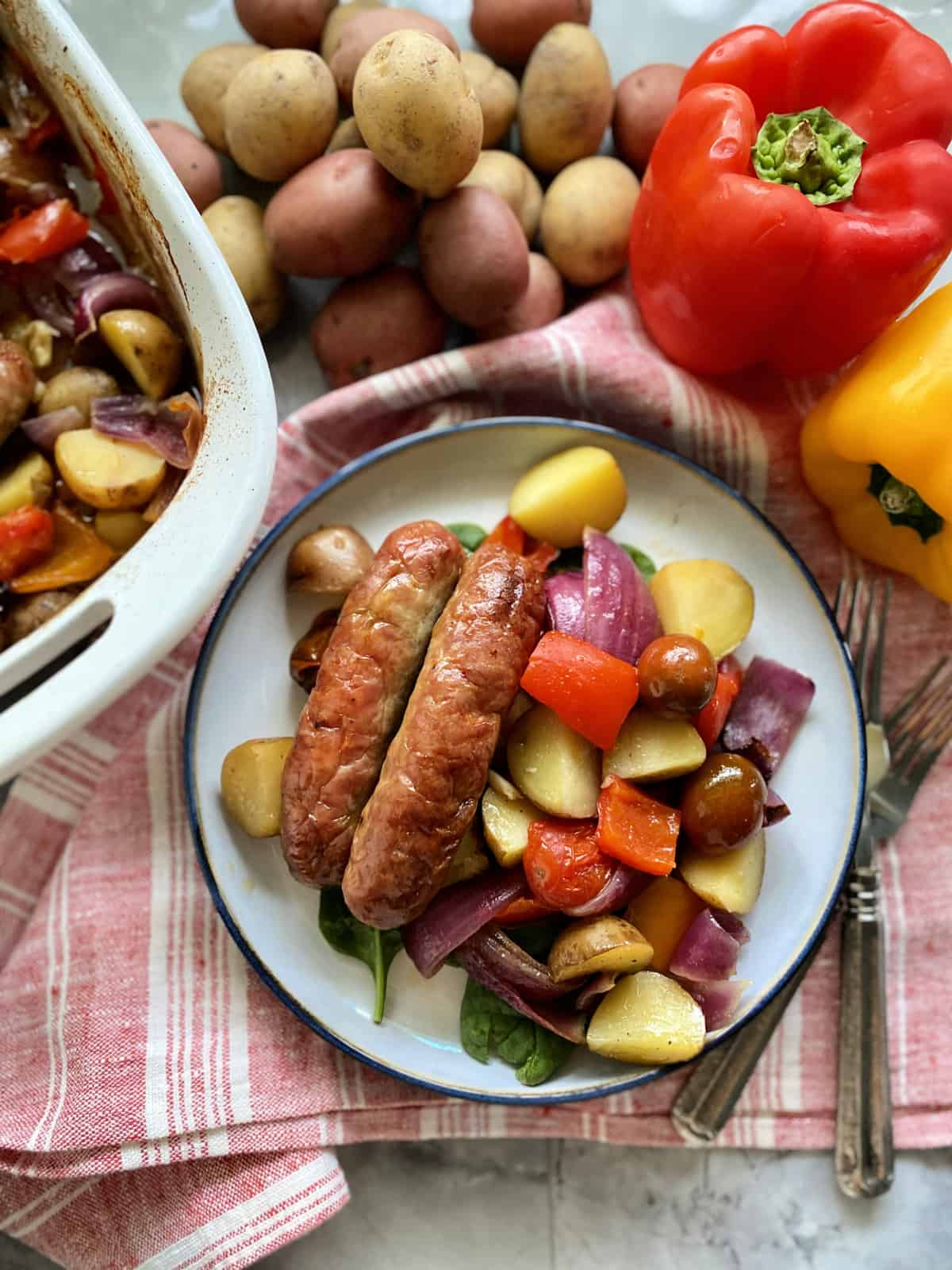 Top view of a plate of Italian sausage with potatoes, bell peppers, and onions.