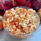 Glass bowl filled with orange popcorn with fall leaves in background.
