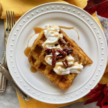 Top view of a white plate with two rectangular waffles with whipped cream and pecans.