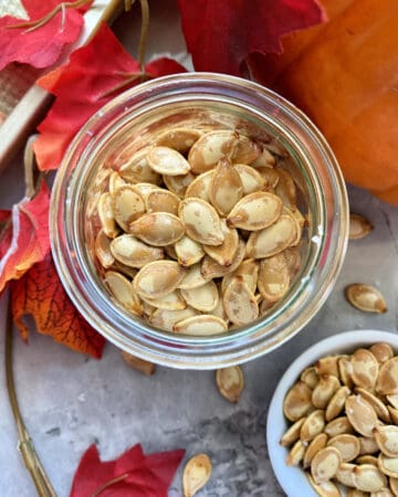 Top view of a glass jar fileld with roasted pumpkin seeds.