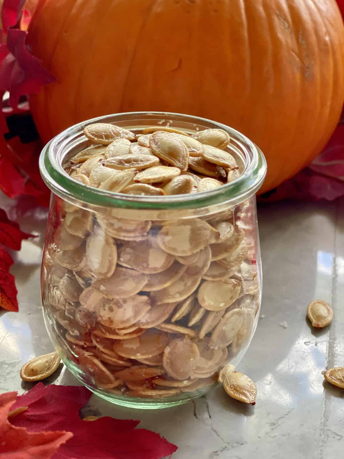 Glass jar filled with roasted pumpkin seeds.