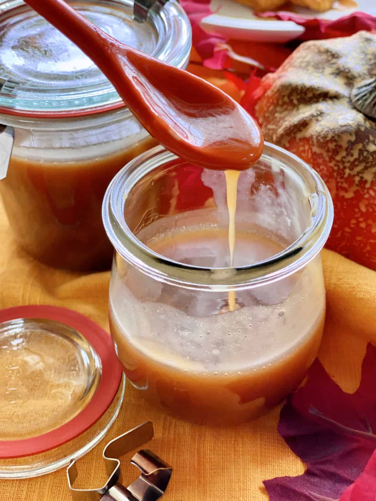 Two glass jars filled with caramel sauce with an orange spoon dripping caramel.