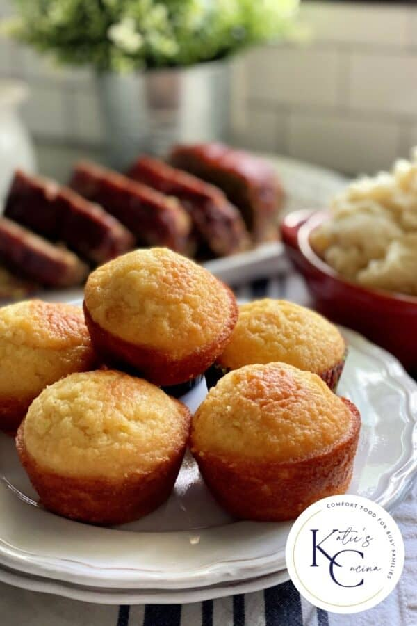 Cornbread muffins stacked on a two white plates with logo on the corner of photo.