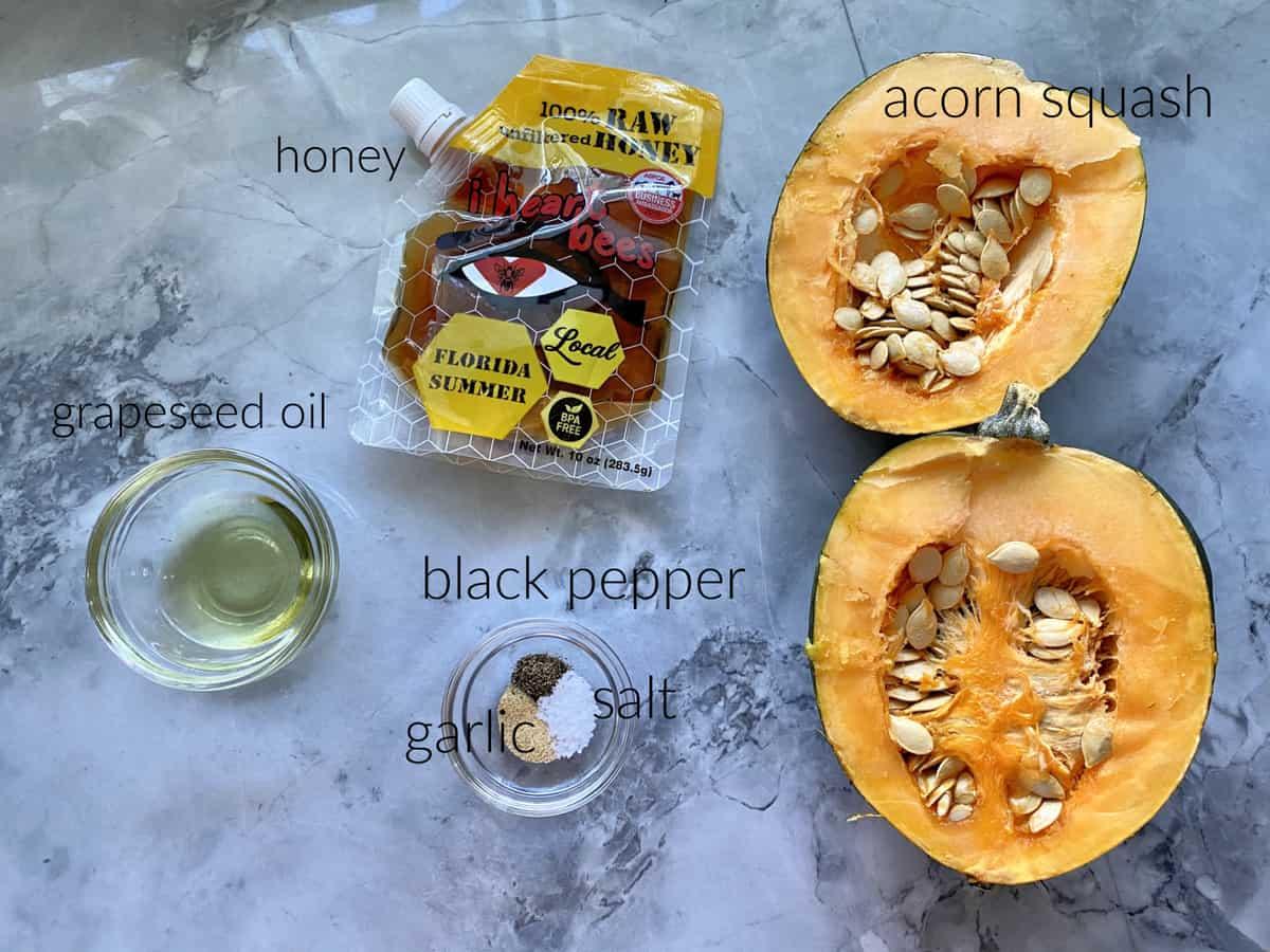 Ingredients: acorn squash, honey, grapeseed oil, seasonings on a marble countertop.