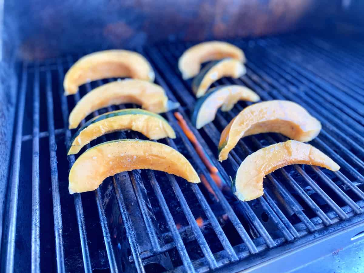 Sliced acorn squash cooking on a grill top.