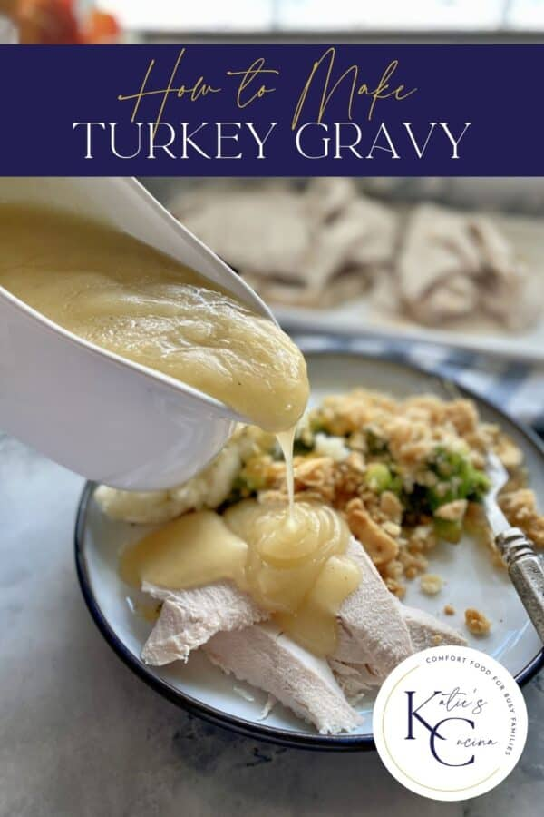 Gravy being poured out of a gravy boat onto a plate of sliced turkey.