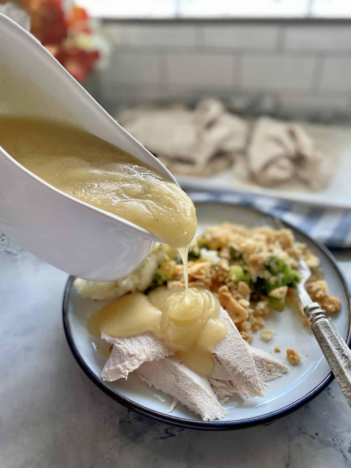 Gravy boat pouring gravy on top of sliced turkey breast.