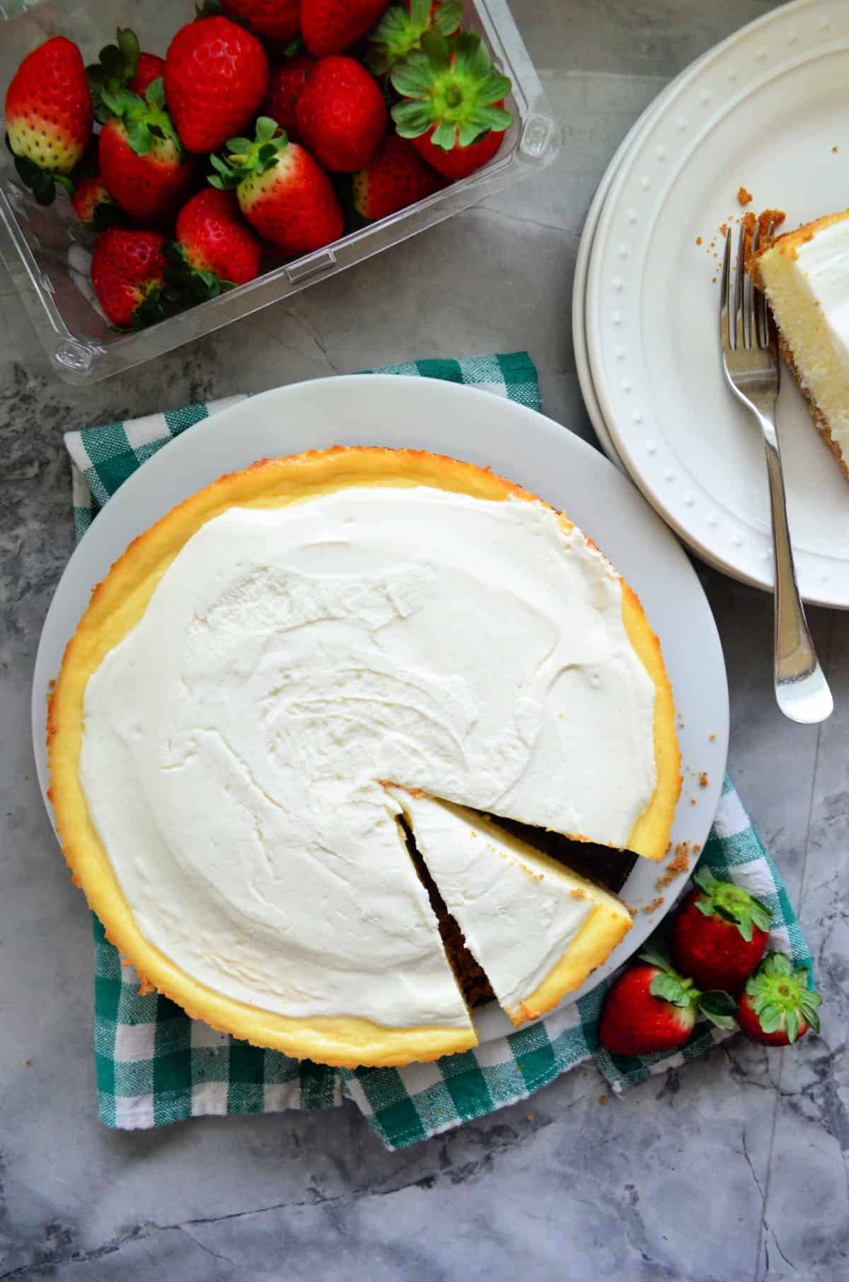 Top view of a sliced plain cheesecake with fresh strawberries on the side.