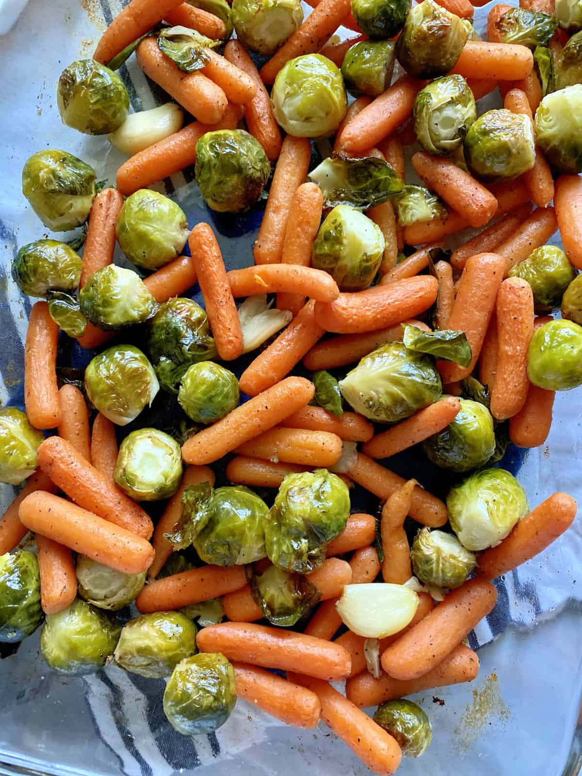 Top view of a glass baking dish filled with Roasted Brussels Sprouts cloves of garlic, and baby Carrots.