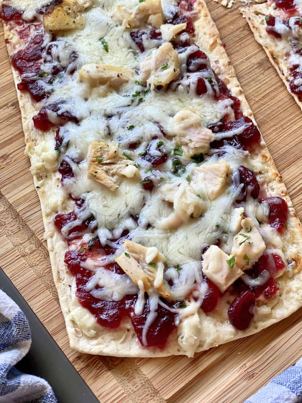 Top view of a single flatbread with turkey, mozzarella and cranberry sauce.