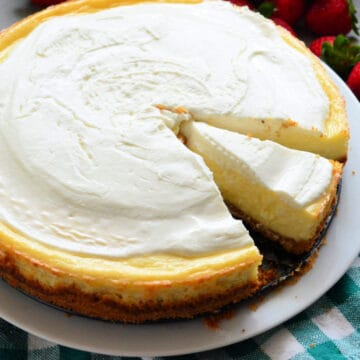 Plain cheesecake with a slice of cheesecake missing with strawberries in the background.