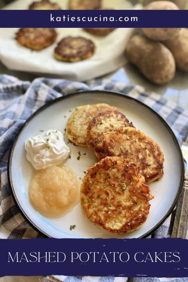 Plate of potato cakes with sour cream and applesauce next to it with text on image for Pinterest.