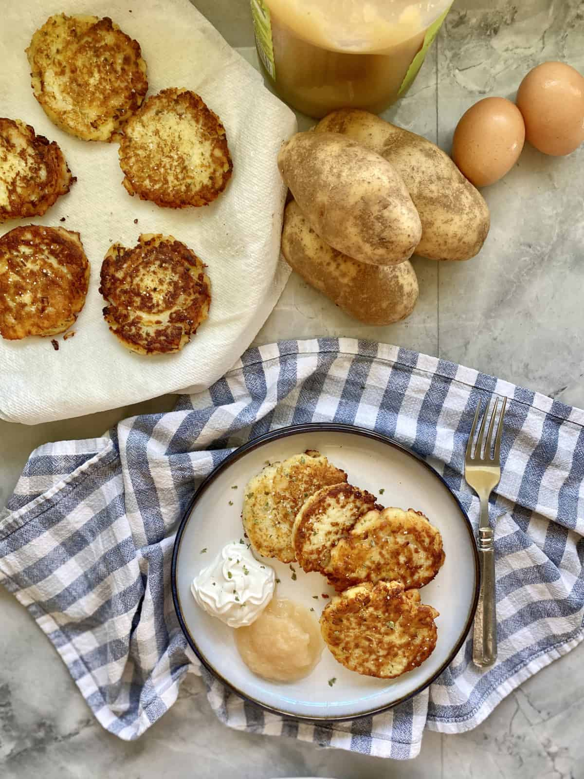 Top viiew of potato pancakes on a plate with potatoes and eggs near by.