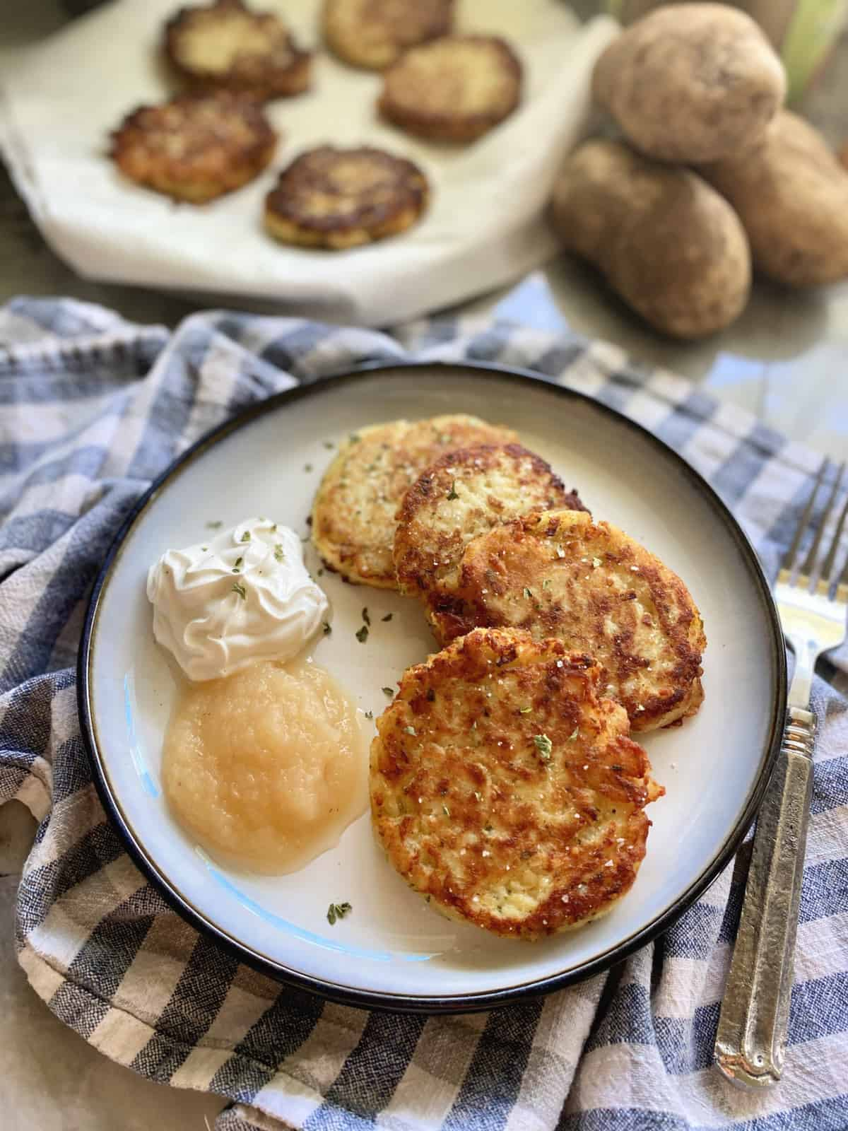 Plate of four mashed potato cakes with sour cream and applesauce next to it.