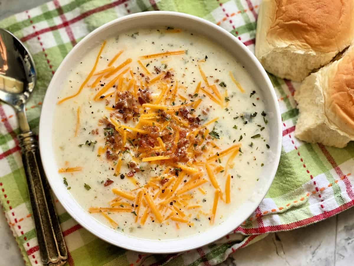 Top view of a bowl of potato soup with cheese, bacon, and herbs with two rolls next to the bowl.