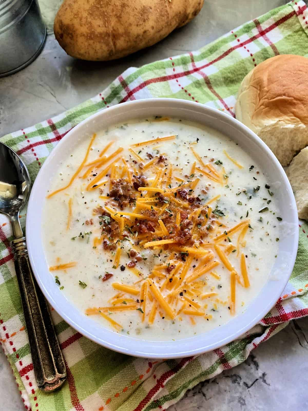 Top view of a bowl of mashed potato soup topped with bacon, cheese, and herbs.