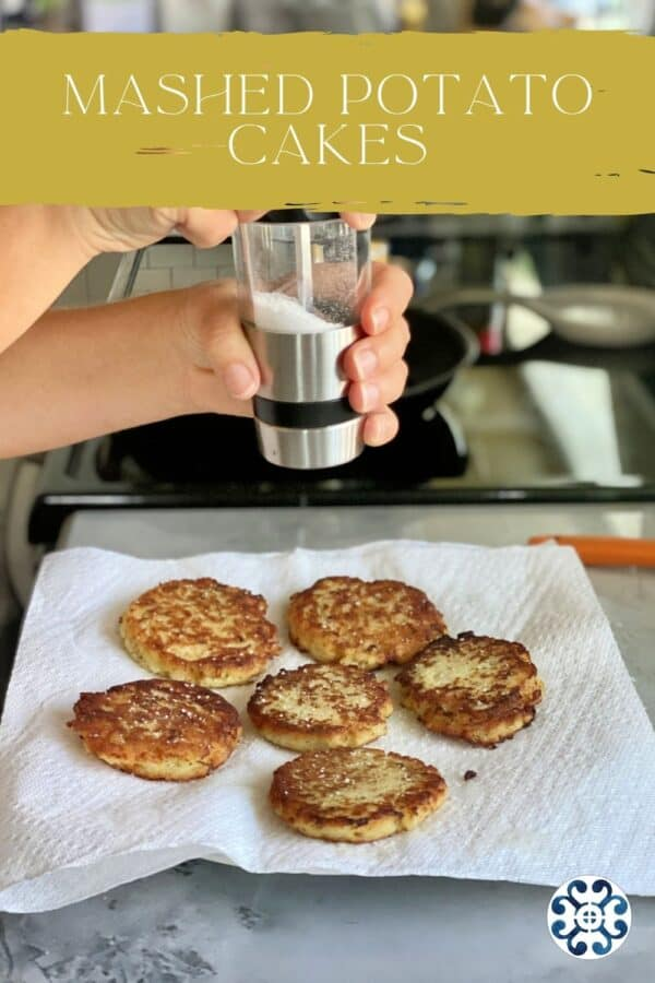 Female hand grinding salt on top of potato cakes on a paper towel lined plate with text on image for Pinterest.
