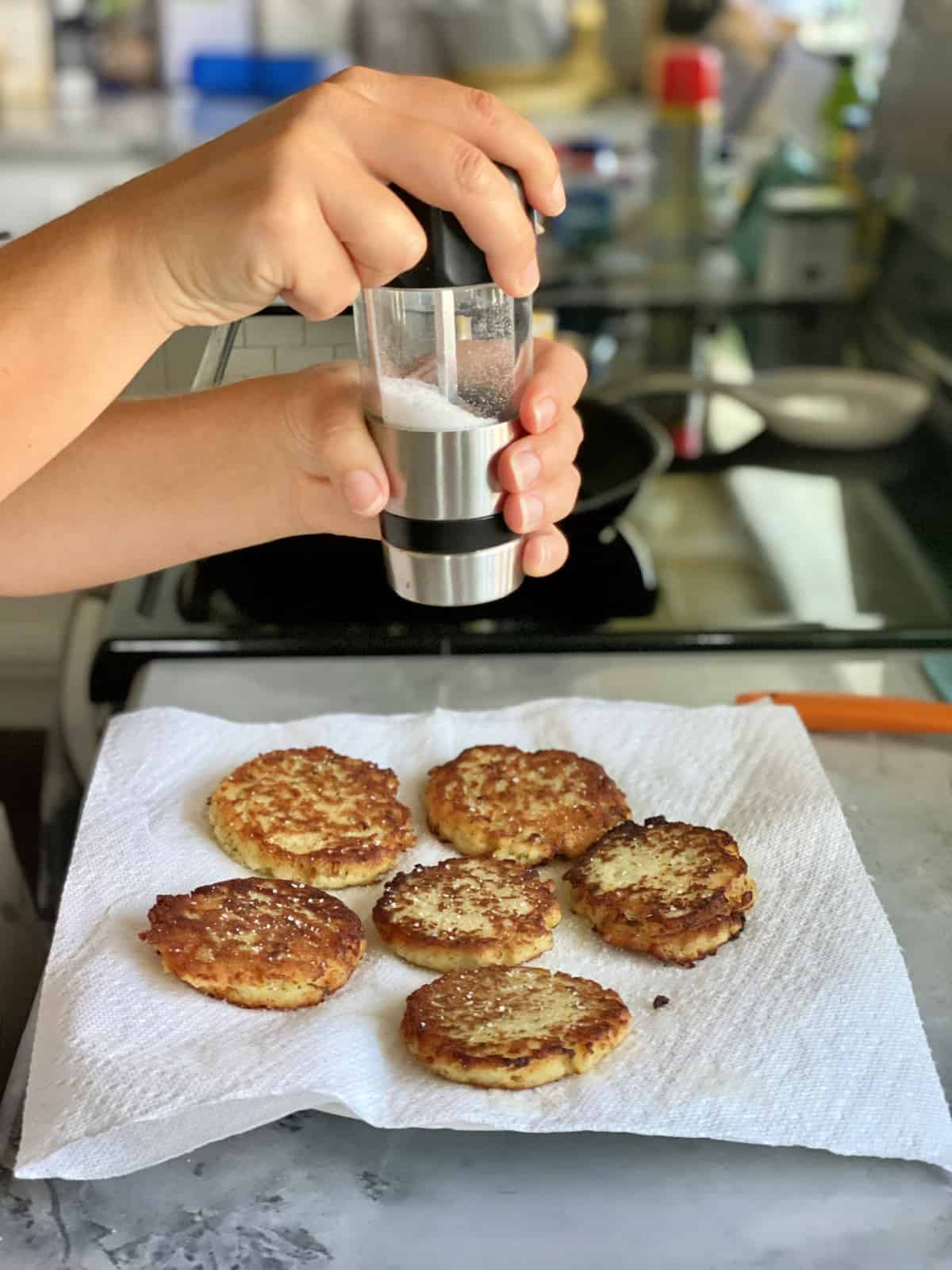 Female hand grinding salt on top of potato cakes on a paper towel lined plate.