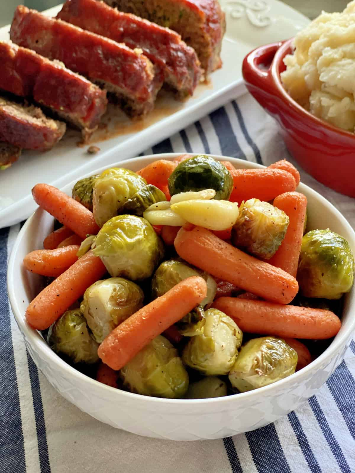 White bowl filled with roasted baby carrots, garlic cloves, and brussels sprouts.