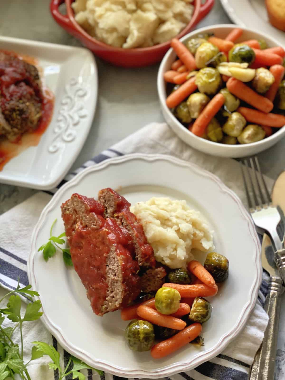 Top view of a plate of meatloaf, mashed potatoes, and veggies, with sides around it.