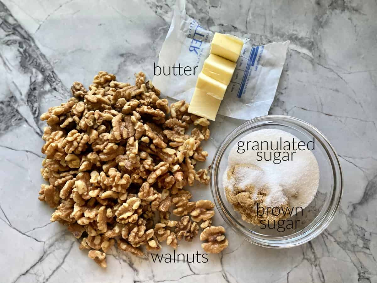 Ingredients: walnuts, butter, brown sugar, and granulated sugar in a glass bowl.