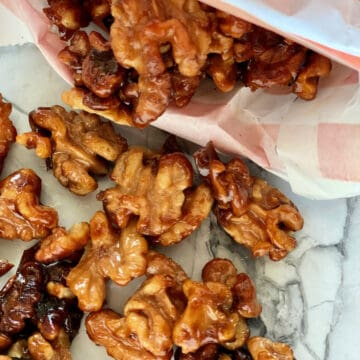 Close up of candied walnuts spilling out of an orange and white bag.