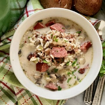 Top view of a white bowl filled with sausage, mushroom, parsley, and rice soup.