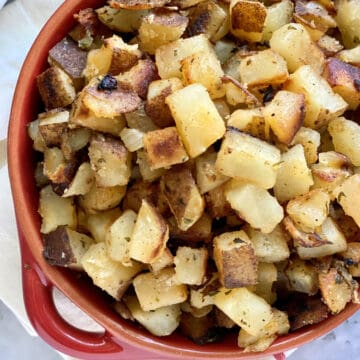 Top view of a red bowl filled with diced crispy breakfast potatoes.