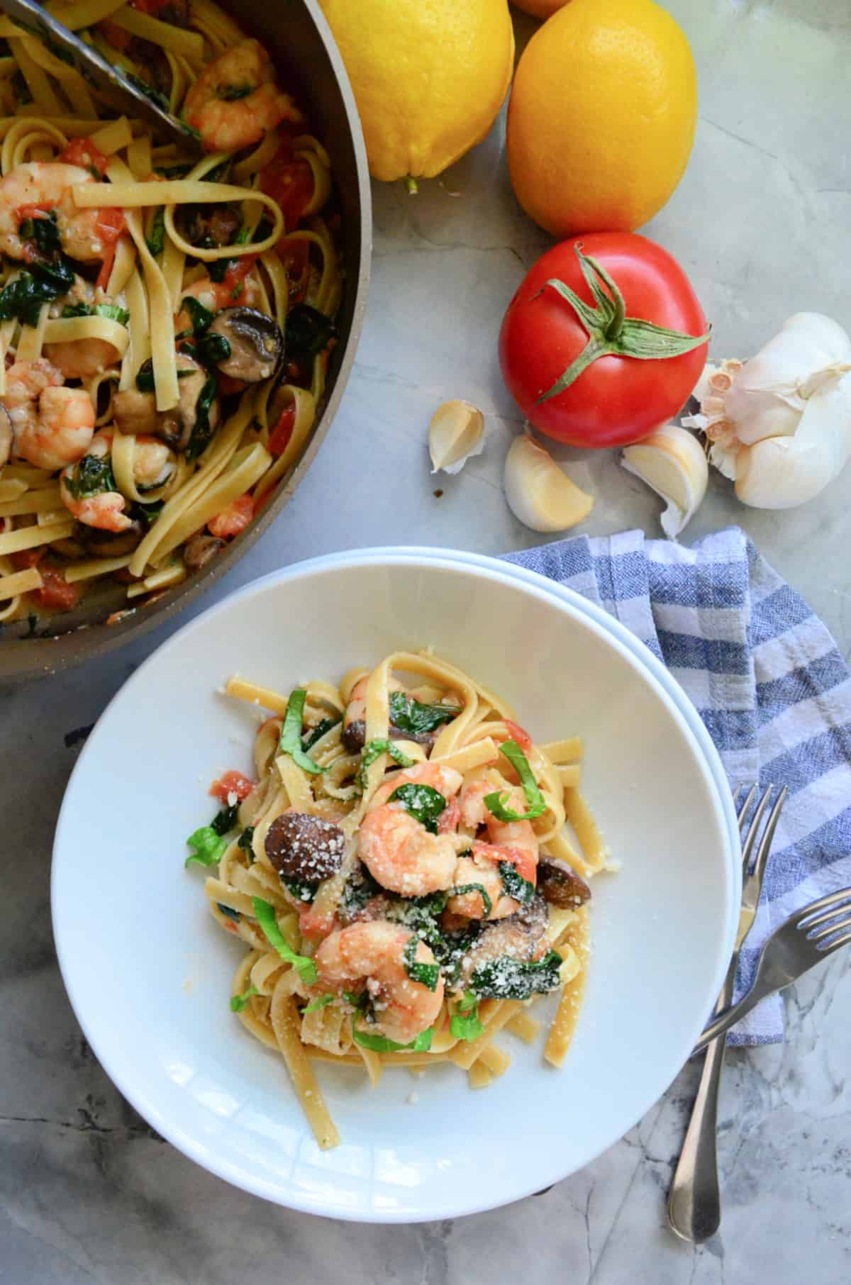 Top view of a white bowl of shrimp pasta with skillet next to it.