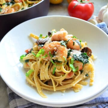 Two shallow white bowls with linguini and shrimp topped with basil ribbons.