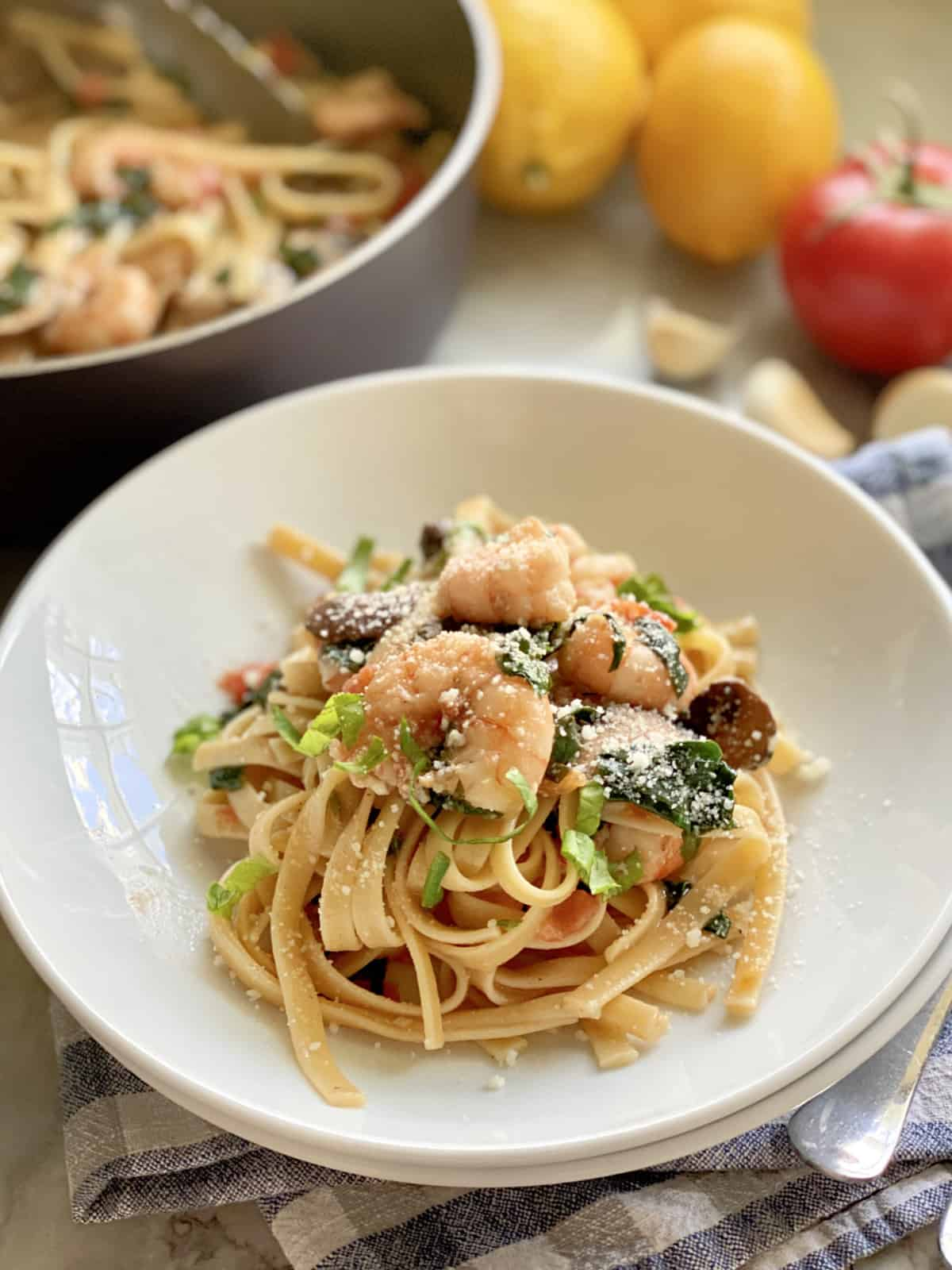 Linguini topped with shrimp nestled in a white bowl.