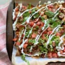 Sheet pan lined with parchment paper with loaded nachos on top.
