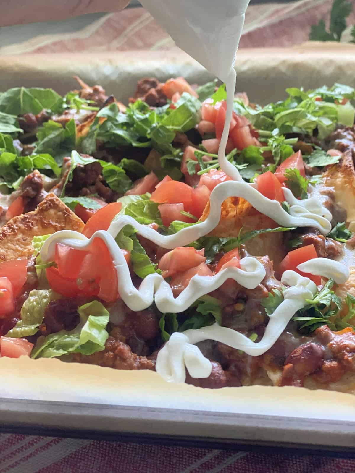 Sour cream drizzling over a sheet pan of nachos.