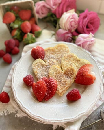 Top view of heart pancakes on a white plate with heart shaped pancakes.