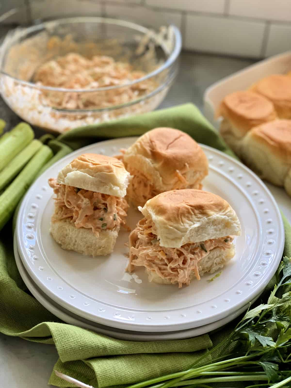 Three buffalo chicken sandwiches on white plate.