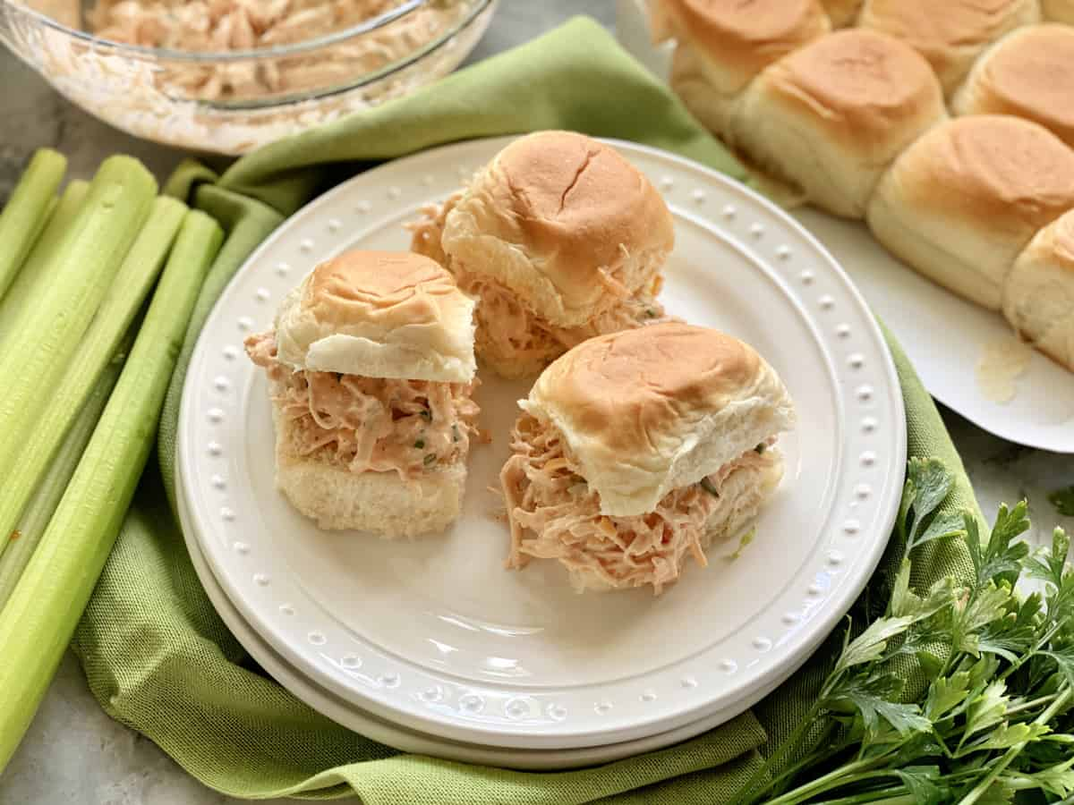 Three chicken salad sandwiches on a white plate with rolls and celery in the background.