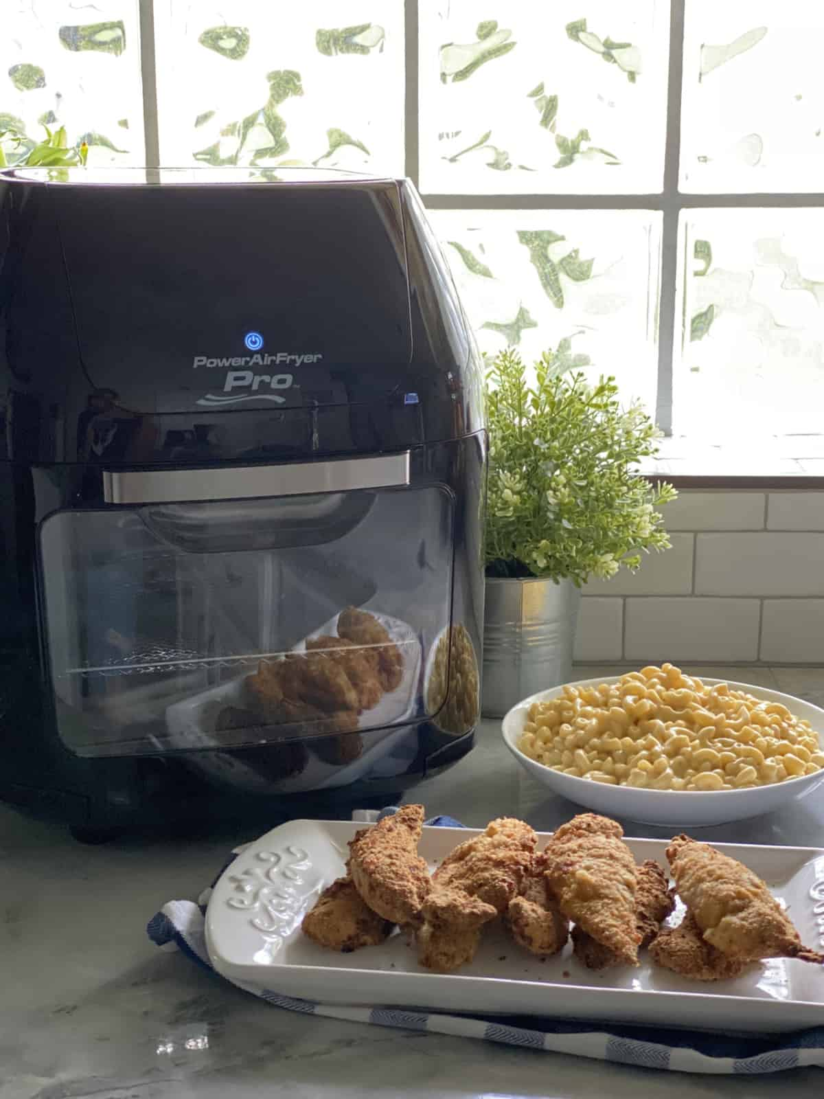 White platter filled with stacked chicken tenders with mac and cheese and Air Fryer in the background.