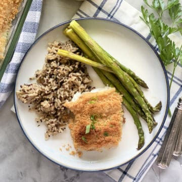Top view of a piece of breaded fish on a white plate filled with wild rice and asparagus.
