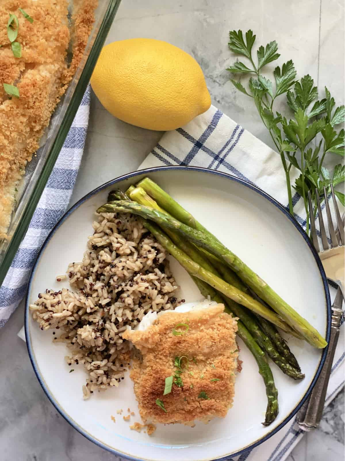 Top view of a white plate with breaded fish, asparagus, and wild rice.