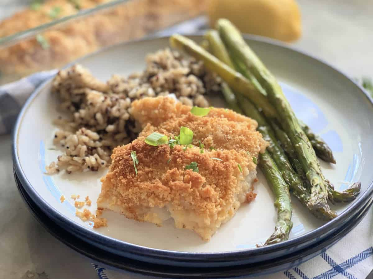 Breaded fish on a plate next to asparagus and rice with glass baking dish in background with fish.