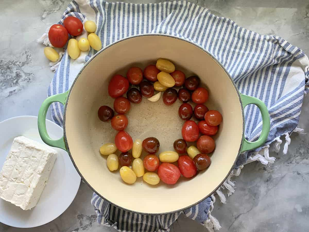 Top view of a green pot with grape tomatoes and garlic.