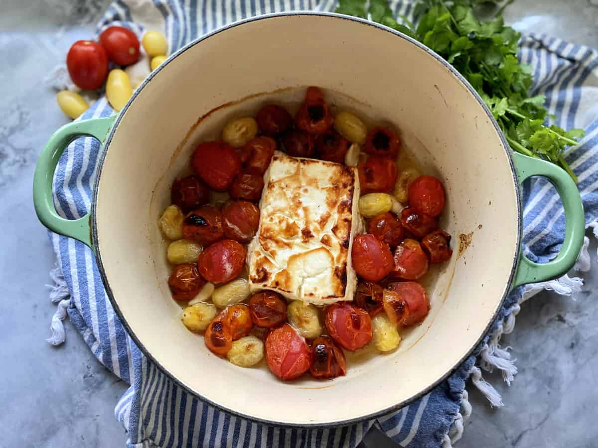 Top view of baked feta with blistered tomatoes in a green pot.