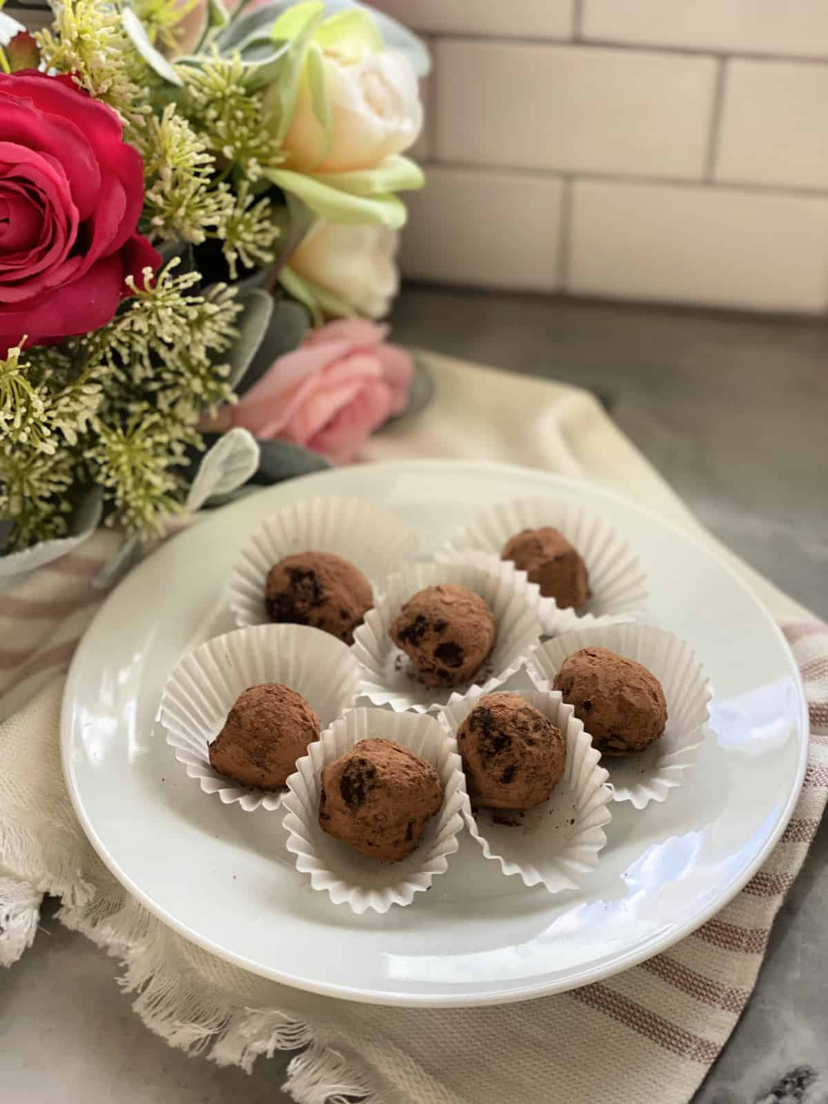White plate filled with 7 cocoa dusted chocolate truffles with roses in background.