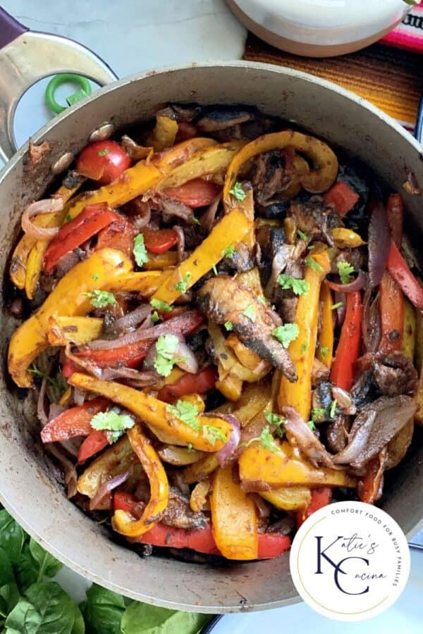 Top view of a skillet with peppers, onions, and mushrooms.