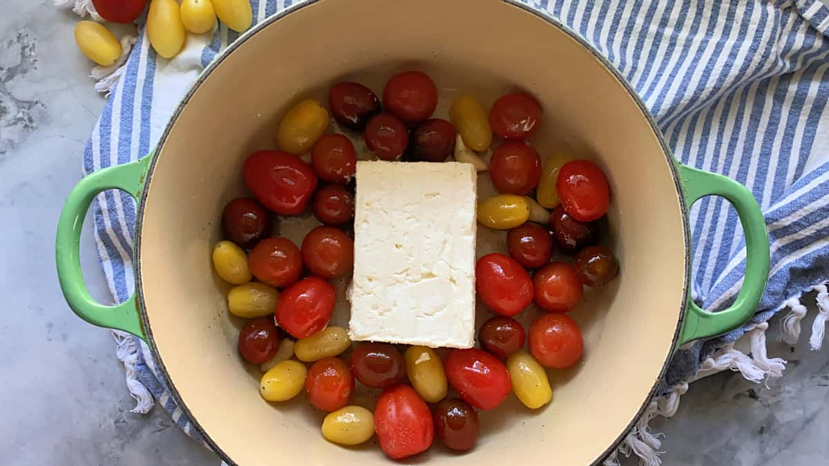 Top view of a block of feta with grape tomatoes in a green pot.