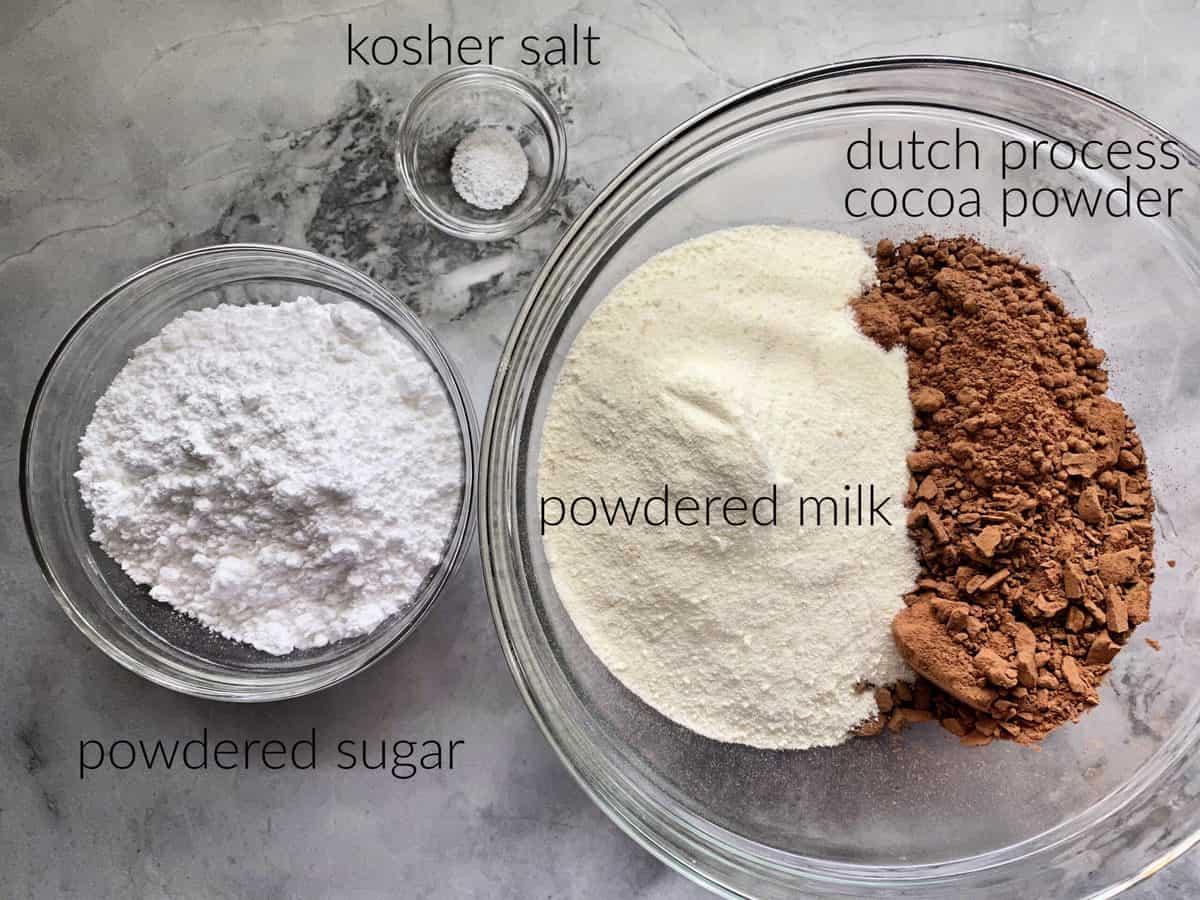 Ingredients on marble countertop: powder milk, cocoa powder, salt, and powder sugar.