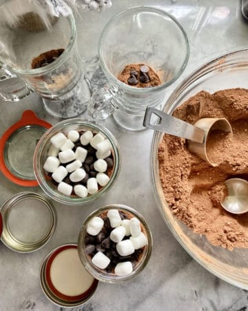 Top view of a bowl of hot chocolate mix with mason jars filled with mix plus marshmallows and chocolate chips.